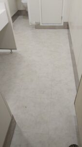 General use bathrooms floor with vinyl tiles & inox skirting board