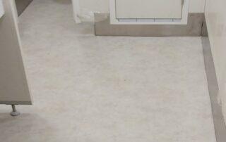 General use bathrooms floor with vinyl tiles & inox skirting board